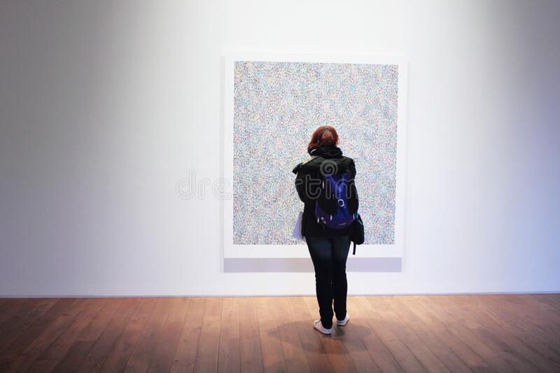Woman Standing Infront of a Wall Mount Painting stock photos