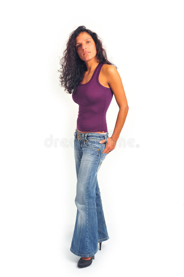 Woman standing in jeans. Woaman standing in jeans and purple top and high heels stock photo