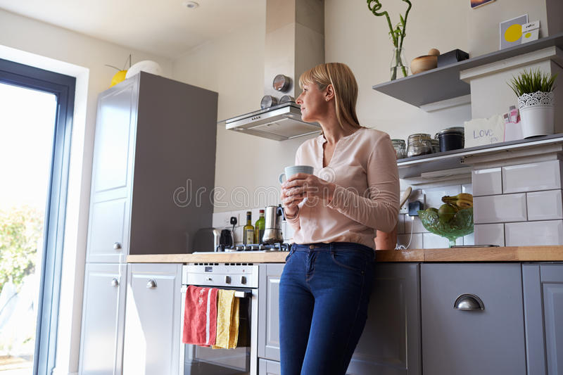 Woman Standing In Kitchen With Hot Drink royalty free stock photo