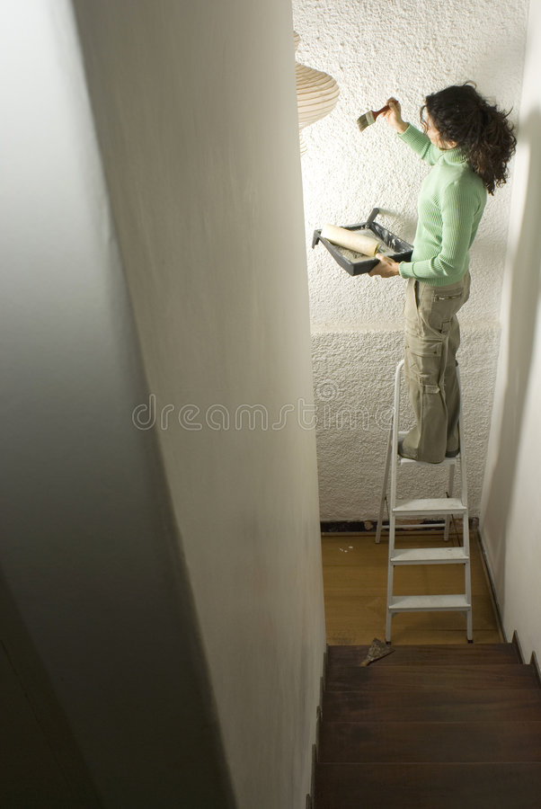 Woman Standing on Ladder Painting Wall stock photography