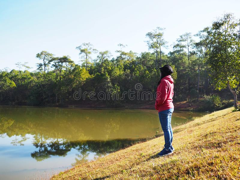 Woman standing at lake side and looking at green forest stock photography