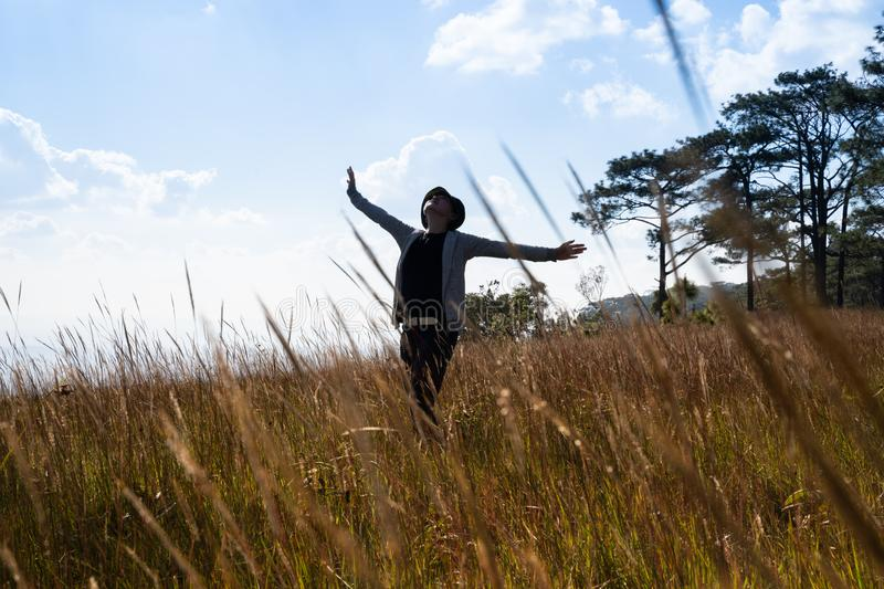 A woman standing in large field enjoying the nature under beautiful blue sky stock image