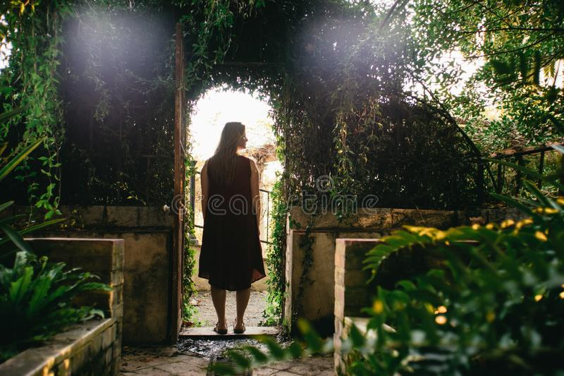 Woman standing in a leafy green arched entrance stock photos