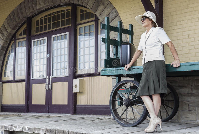 Woman standing and leaning against an old retro luggage cart by train station entry door. royalty free stock images