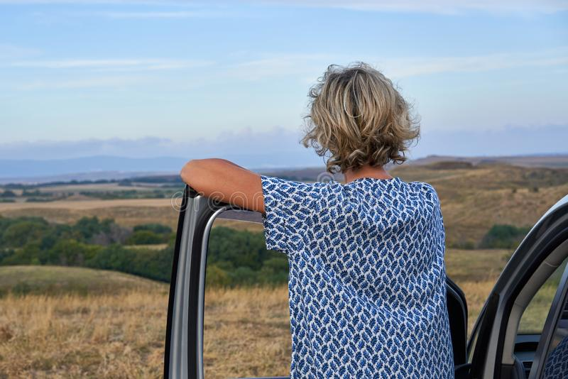 Woman standing leaning on a car door. Looking into the distance, on countryside on twilight, back view stock photo