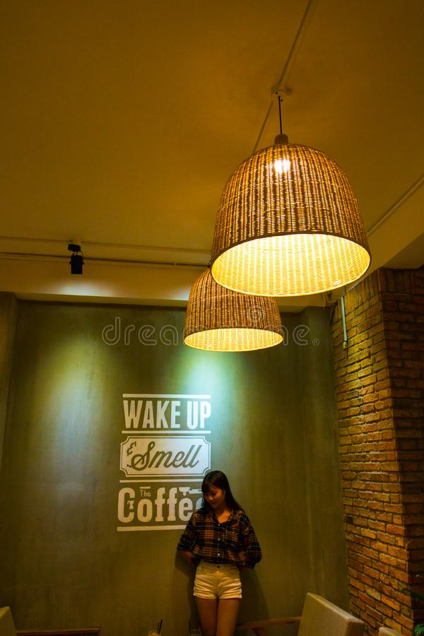 Woman Standing and Leaning Beside Wake Up Smell the Coffee Text Wall stock image