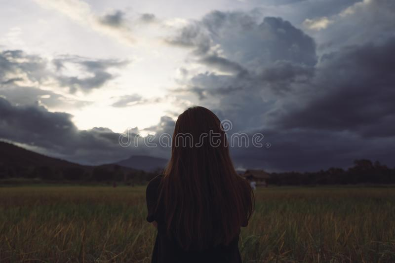 A woman standing and looking at a beautiful rice field onward with feeling relaxed. And calm stock image