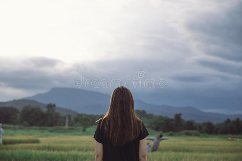 A woman standing and looking at a beautiful rice field onward with feeling relaxed. And calm stock photography