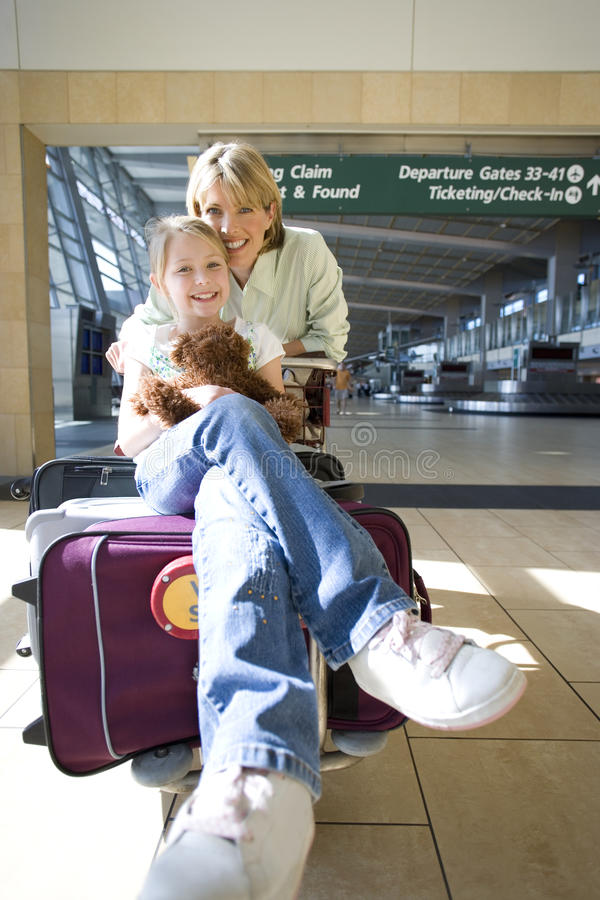 Woman standing beside luggage trolley in airport, daughter (7-9) sitting on suitcase with soft toy, smiling, front view, portrait royalty free stock photo