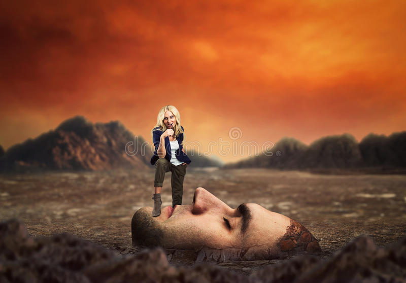 Woman standing on male face stock photo