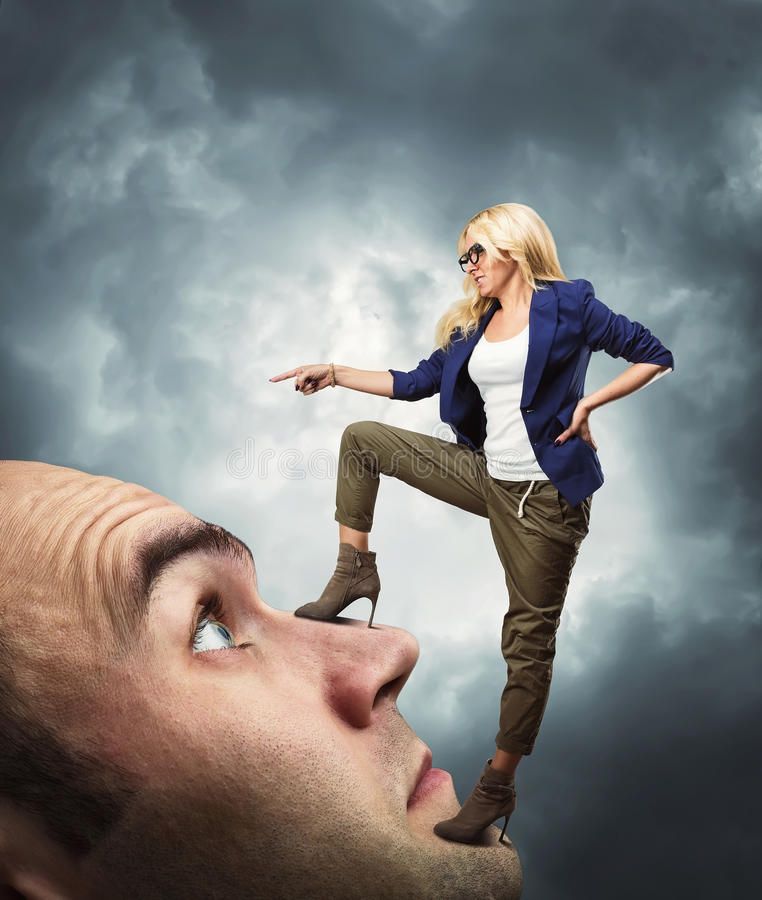 Woman standing on male face royalty free stock images