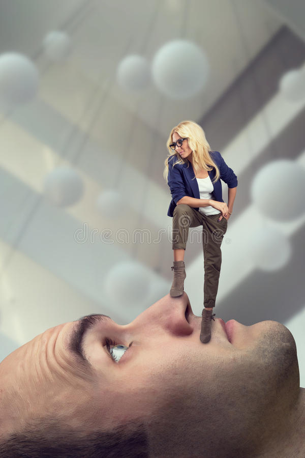 Woman standing on male face royalty free stock image