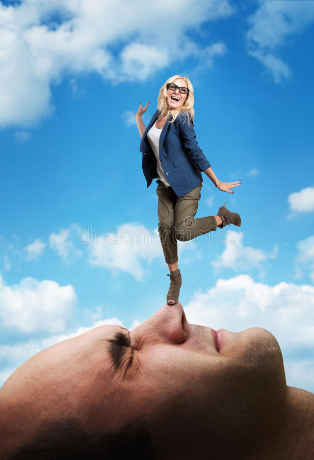 Woman standing on the man's face stock photos