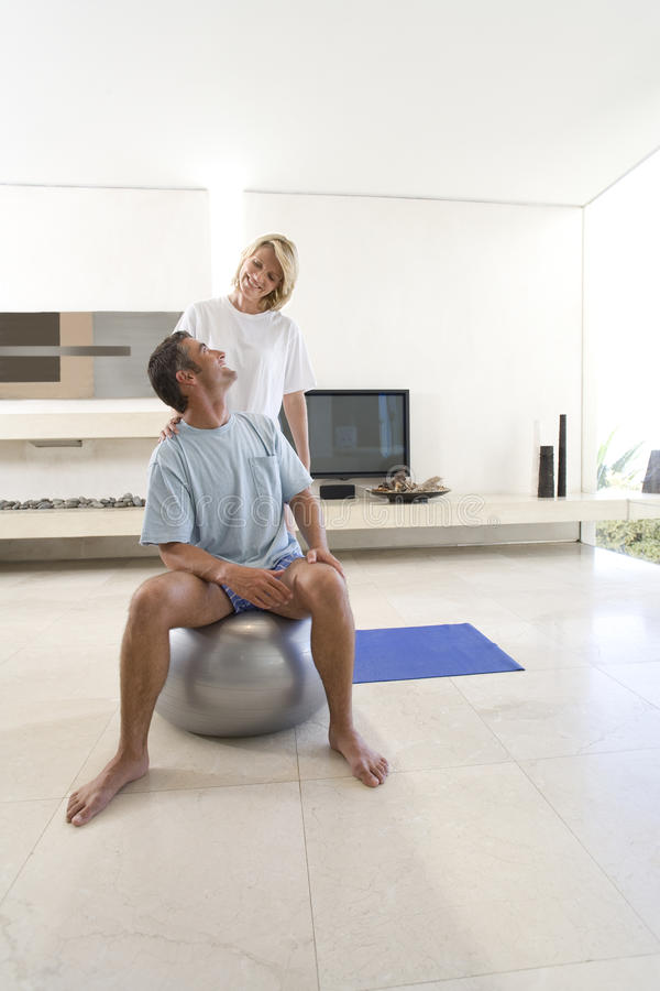 Woman standing by man sitting on exercise ball in living room, smiling at each other stock image