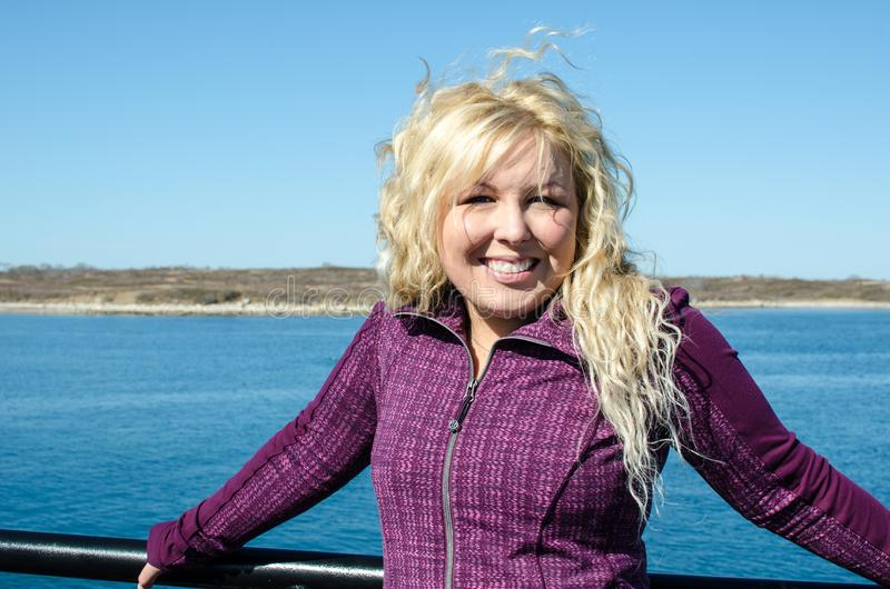 Woman standing on the Marthas Vineyard ferry, enjoying the wind blowing her blonde hair.  stock image