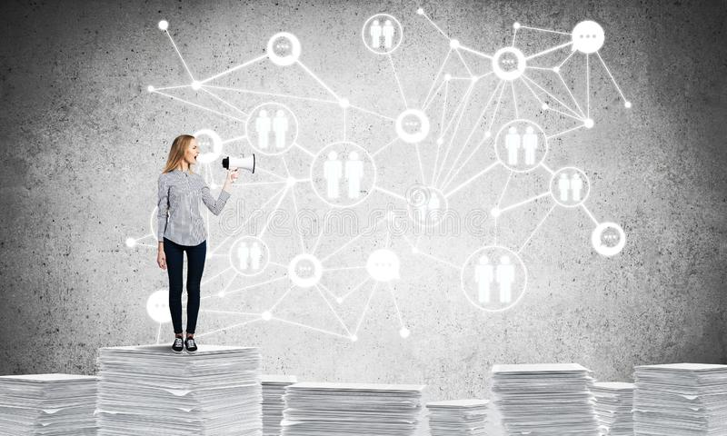 Woman standing with megaphone. Woman in casual wear with speaker in hand standing on pile of documents with social network structure on background. Mixed media stock illustration
