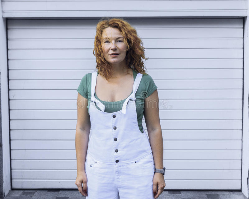 Woman standing on minimalism white pattern in white overalls. Day, outdoor stock image
