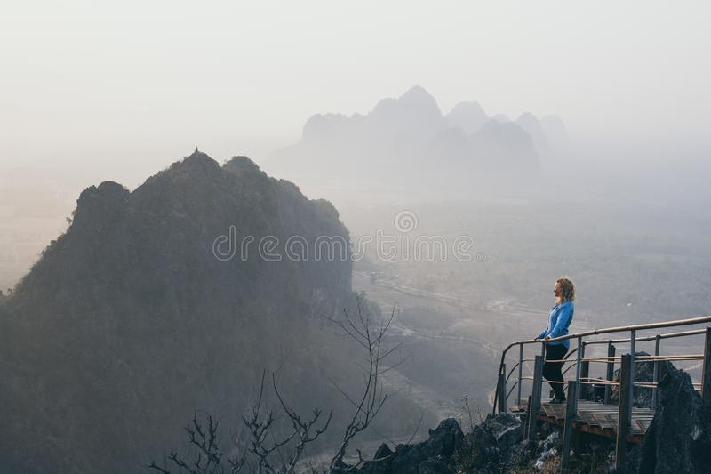 Woman standing on mountain peak with stairs going down during sunrise foggy morning in Hpa-An, Myanmar. Woman in denim shirt standing on mountain peak with royalty free stock photos