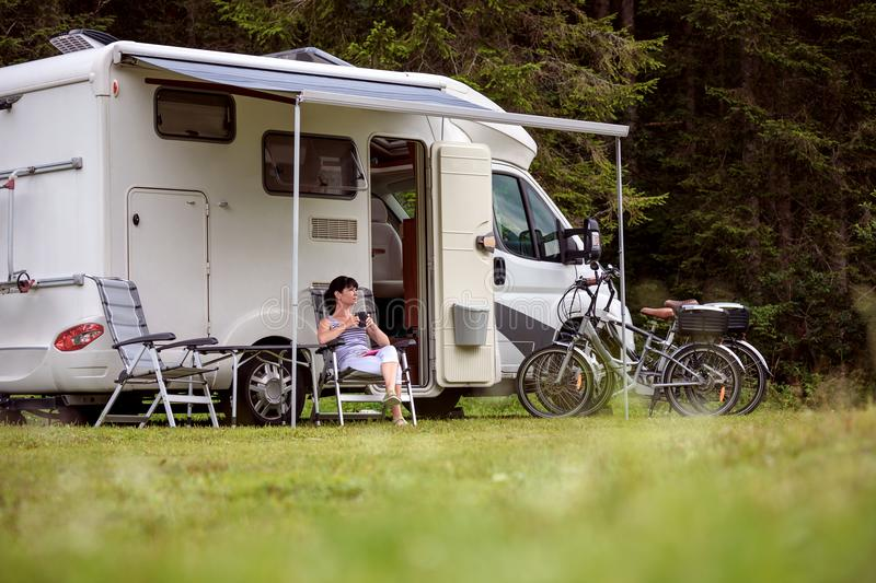 Woman is standing with a mug of coffee near the camper RV. royalty free stock photos