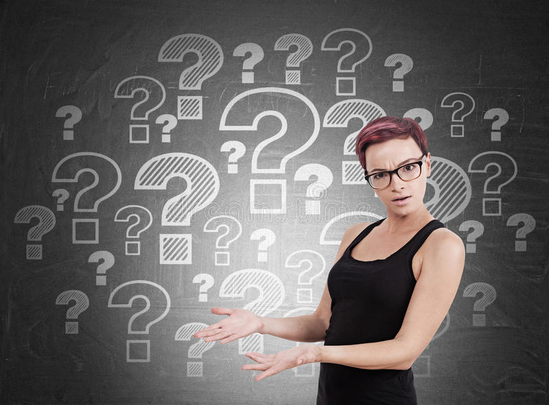 Woman standing near blackboard with question marks royalty free stock photography