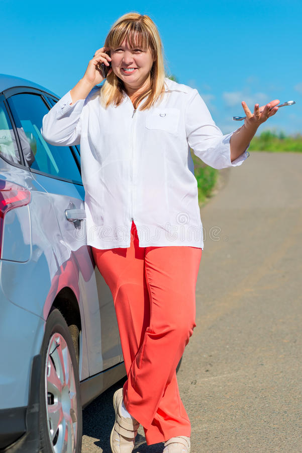 Woman standing near a car with a wrench. Woman standing near a gray car with a wrench royalty free stock photos