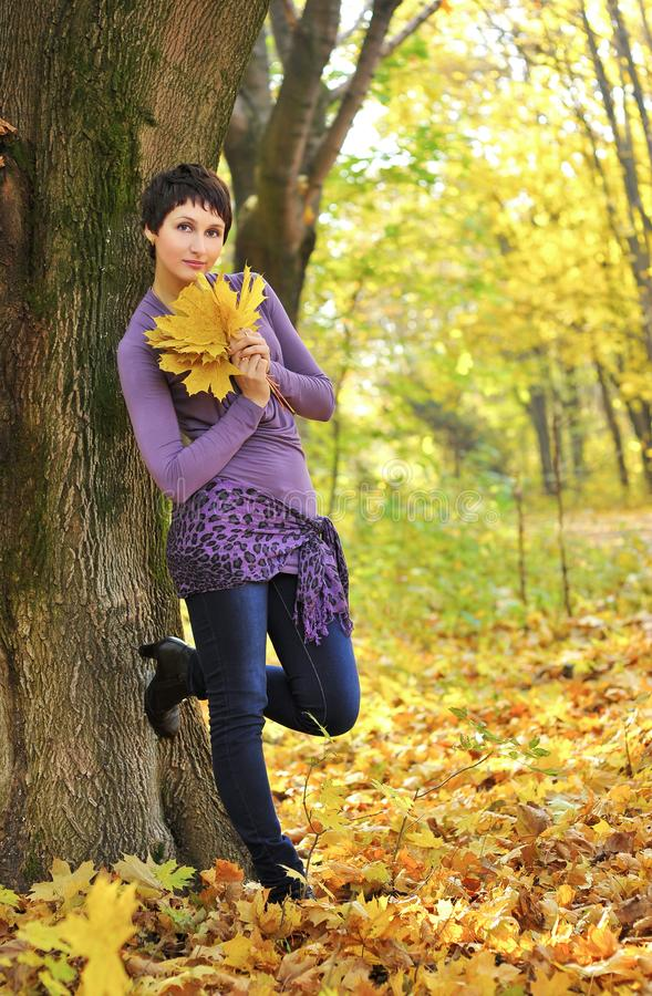 Woman standing near a tree holding a bouquet of maple leaves royalty free stock photo