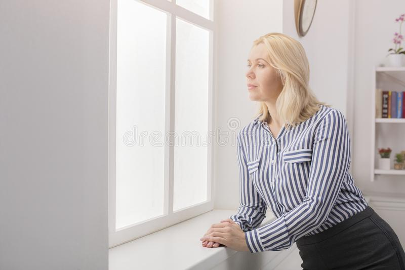 Woman standing near window at her office royalty free stock images
