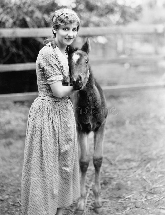 Woman standing next to a pony in a corral stock photo