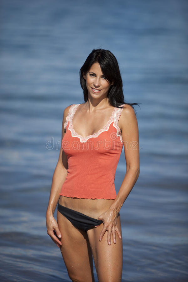 Woman standing next to the water. Female in an orange lace tank top and a black bikini bottom stock photo