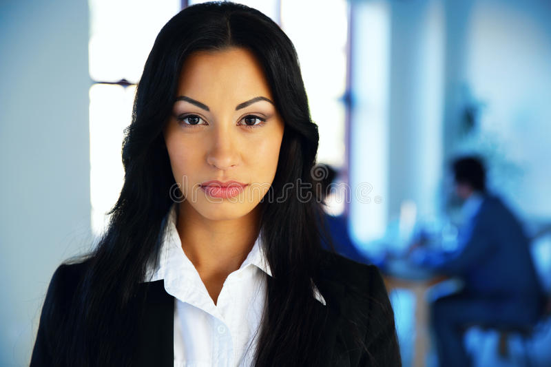 Woman standing in office with colleagues stock images