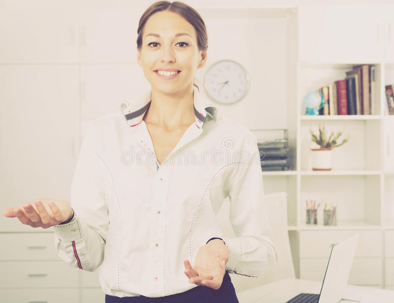 Woman standing in office. Portrait of smiling young business woman standing in firm office royalty free stock photography