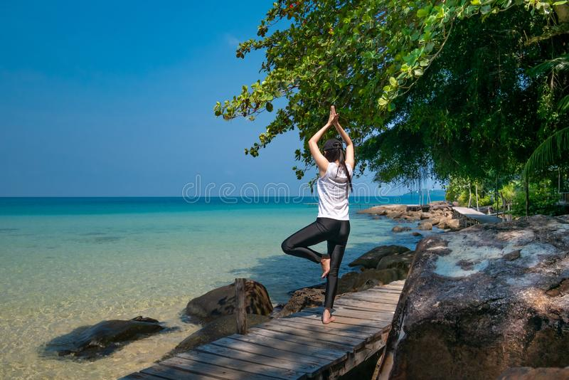 A woman standing on one leg while practicing yoga on wooden bridge over the sea during summer vacation. attractive young Asian royalty free stock photos