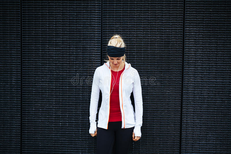 Woman standing outdoors in sportswear looking down. Fitness woman standing against a wall stock image