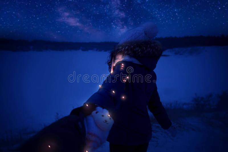 Woman with christmas lights watching stars in winter royalty free stock images