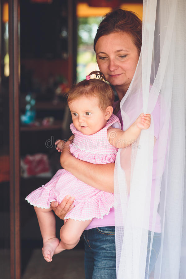 Woman standing at the patio door with her little daughter. On hands royalty free stock photos