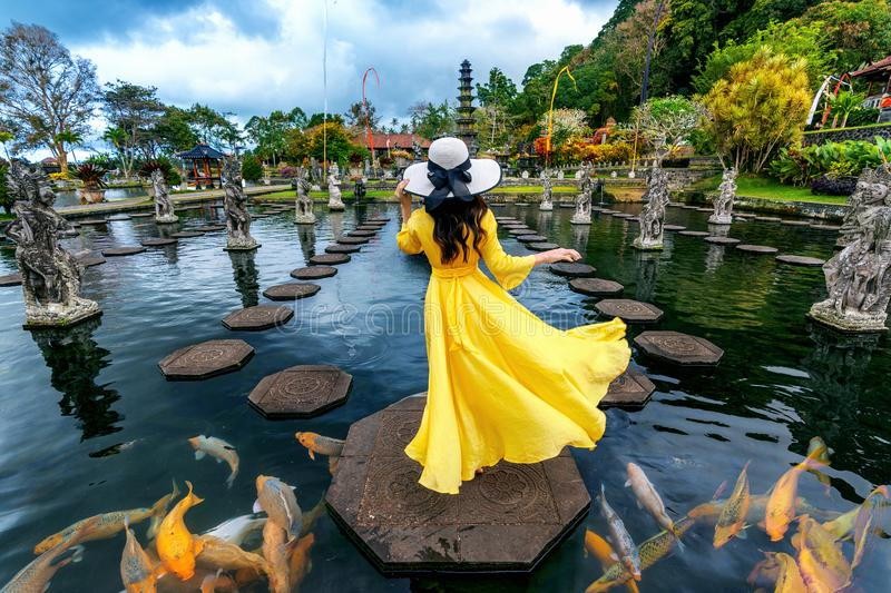 Woman standing in pond with colorful fish at Tirta Gangga Water Palace in Bali, Indonesia. royalty free stock photos