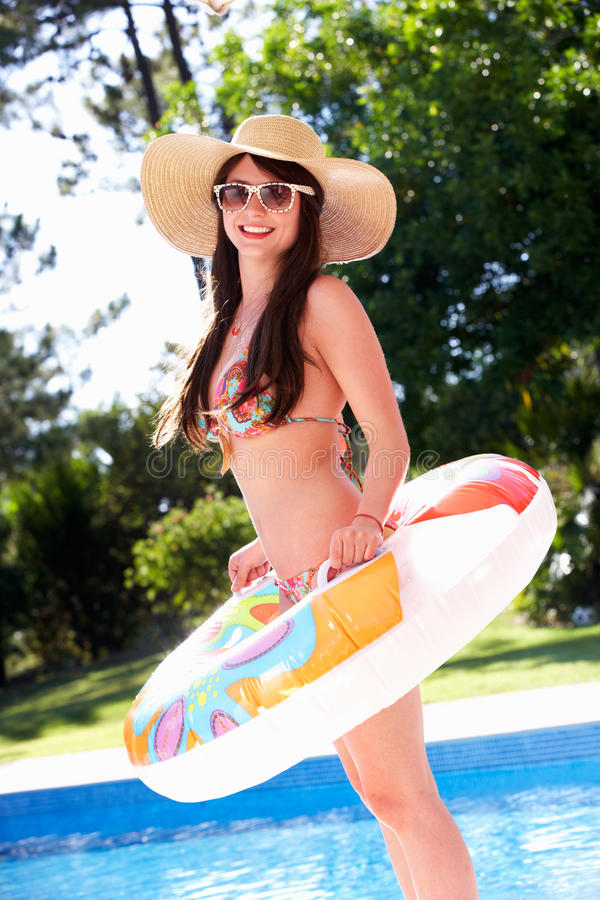 Woman Standing By Pool With Inflatable Ring