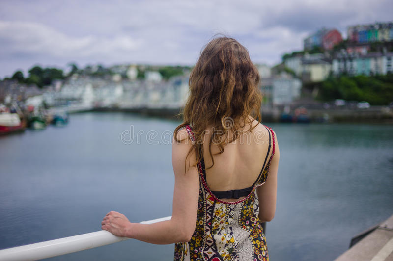 Woman standing by railing in harbor. A young woman is standing by the railing in a small harbor stock image