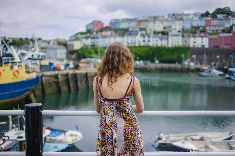 Woman standing by railing in harbor. A young woman is standing by the railing in a small harbor royalty free stock photo