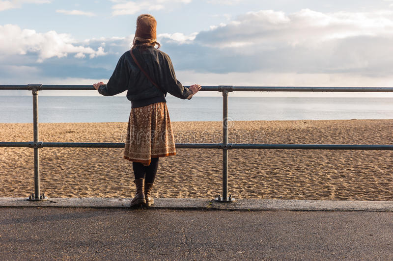 Woman standing by railings on beach stock image