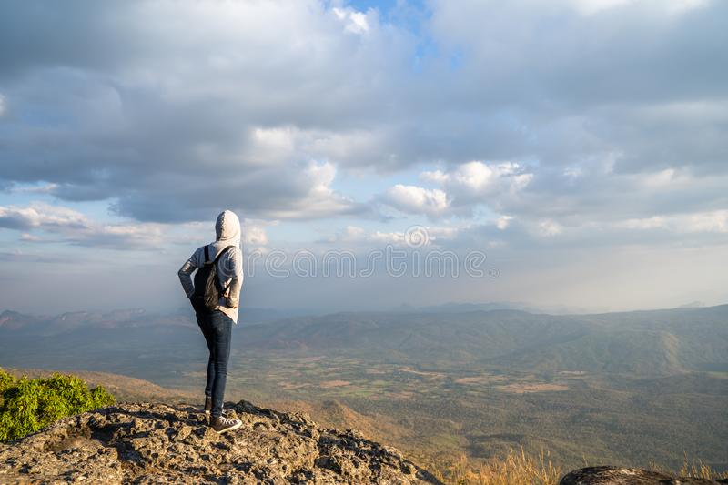 A woman standing on rocky mountain looking out at scenic natural view and beautiful blue sky royalty free stock images