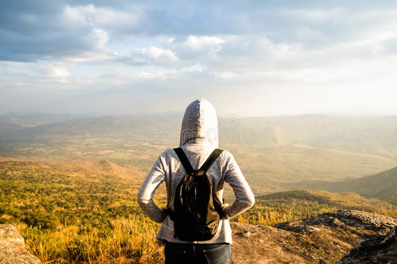 A woman standing on rocky mountain looking out at scenic natural view and beautiful blue sky stock photos