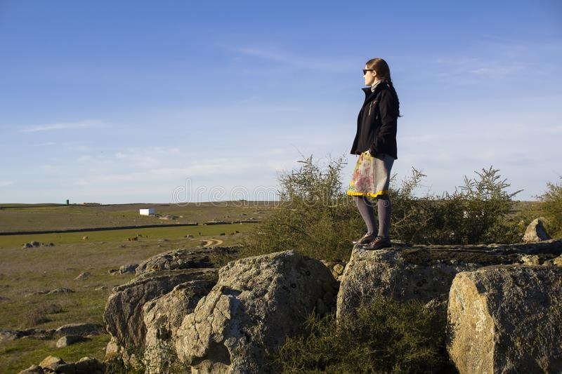 Woman standing on a rocky outcrop. Looking out across the flat plains below enjoying the solitude of the countryside stock images