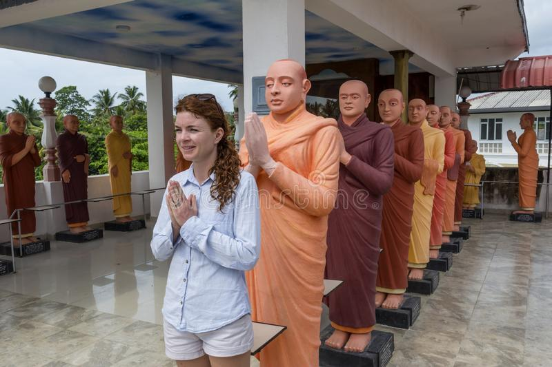 Woman standing in the row with buddhist statues royalty free stock image