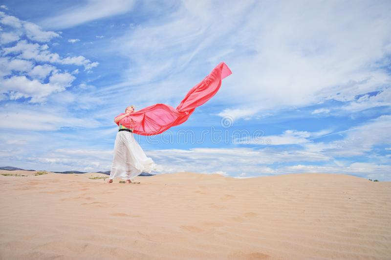 Woman standing in sand dunes stock photography