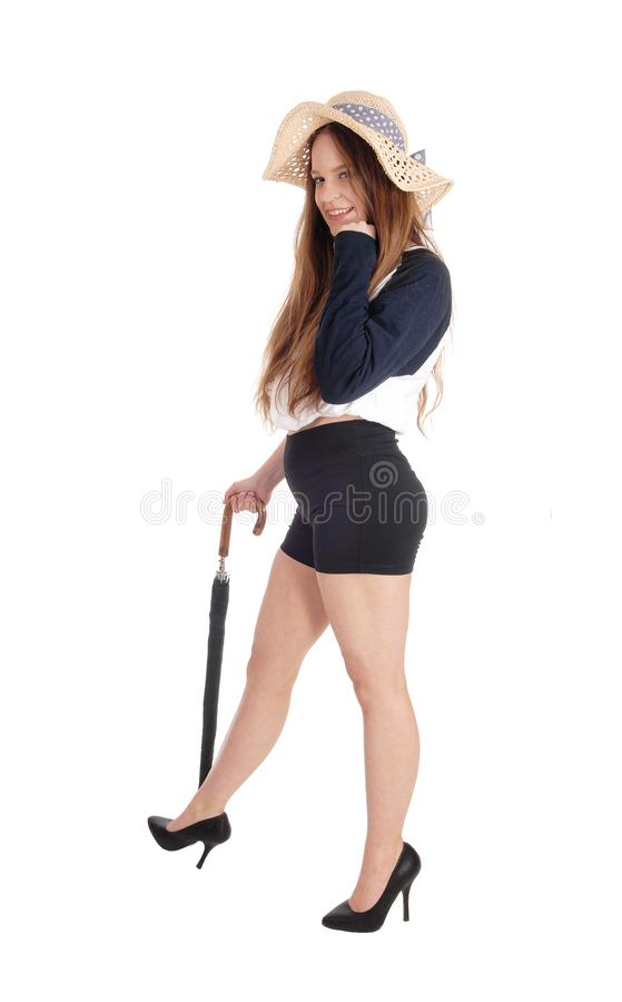 Woman standing in shorts with an umbrella stock image