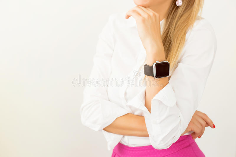 Woman standing with smartwatch around her wrist royalty free stock photo
