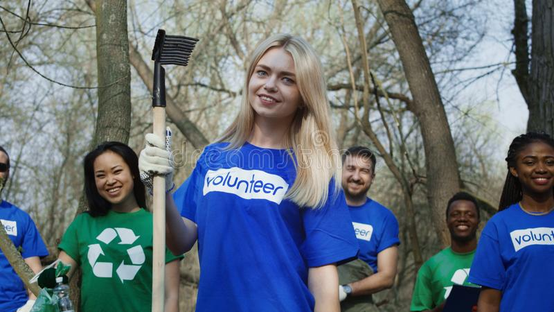 Smiling girl with group of volunteers. Woman standing with smiling multiethnic friends in shirts of volunteers working in team in forest stock image