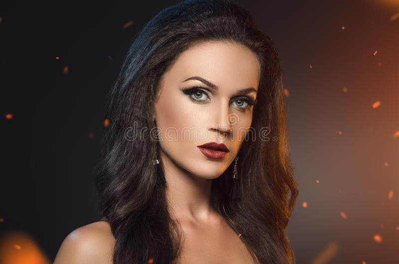 Woman standing in the sparks of fire. Beauty portrait of brunette in black earrings on a dark background royalty free stock photo