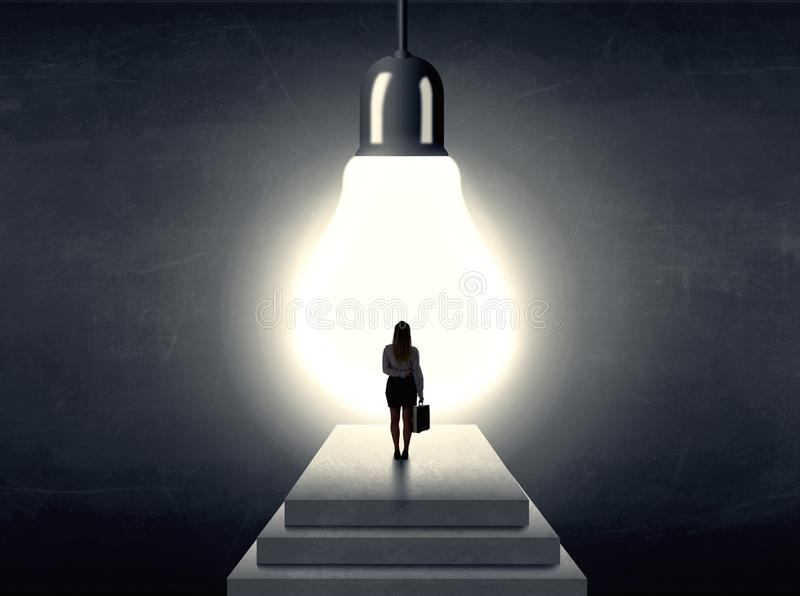 Woman standing on a step in front of a huge light bulb. Businesswoman standing on a step in front of a huge light bulb, concept of having an idea stock images